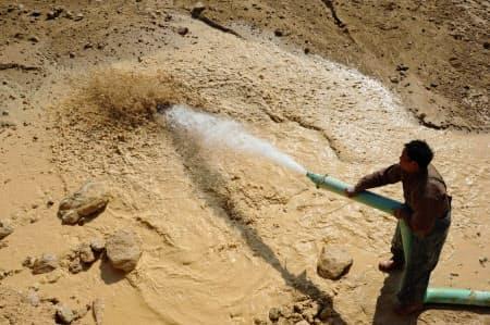 レアアース(希土類)の鉱山で散水する労働者(中国江西省撫州市)=ロイター