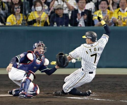 7回阪神2死一塁、大山の左前打が失策を誘い、糸井が一気に生還。捕手中村(22日、甲子園)=共同