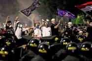 22日、ジャカルタ中心部の総選挙監視庁前で治安部隊と対峙するデモ隊=ロイター