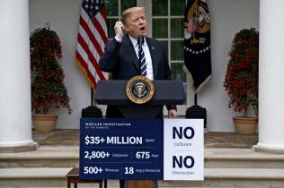 22日、トランプ米大統領は詳細なデータを盛り込んだポスターを使い、ロシア疑惑の潔白をアピールした(ワシントン)=AP