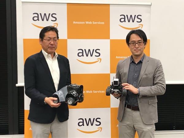 ディープレーサーを手にするアマゾンウェブサービスジャパンの滝沢与一氏(右)と大日本印刷の福田祐一郎氏