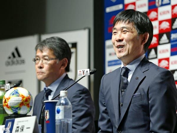 サッカーの国際親善試合に臨む日本代表メンバーを発表する森保監督。左は日本サッカー協会の関塚隆技術委員長(23日、東京都文京区)=共同