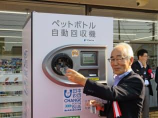 回収機にペットボトルを入れる東大和市の尾崎保夫市長