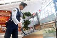 トランプ米大統領の来日を控え、羽田空港国際線ターミナルのゴミ箱を調べる警視庁東京国際空港テロ対処部隊の隊員(23日)