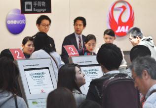 旅客システムに不具合が発生し、搭乗手続きで混雑する日本航空のカウンター(8日午前、羽田空港)