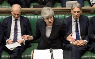 メイ英首相(中)への辞任圧力が保守党内で高まっている(22日、ロンドン)=ロイター
