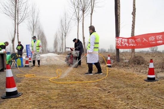 アフリカ豚コレラが見つかった農場周辺で作業する警察官ら(2月、河北省)=ロイター