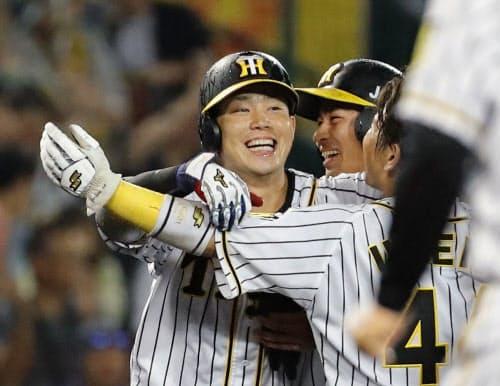 9回、サヨナラ打を放ち、ナインに祝福され笑顔の阪神・糸原=左(23日、甲子園)=共同