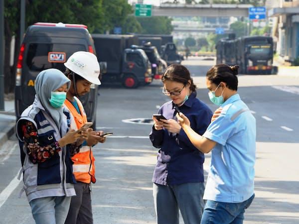 SNSや対話アプリの利用制限は市民の日常生活に影響を与える可能性がある(23日、ジャカルタ中心部でスマホを利用する若者)