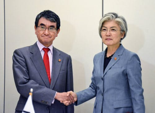 韓国の康京和外相(右)と握手する河野外相(23日、パリ)=共同
