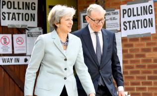 英国のEU離脱案が紛糾する中で、自宅のあるソニングで夫のフィリップ氏と共に欧州議会選の投票を済ませたメイ英首相=ロイター