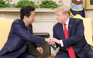 握手する安倍首相(左)とトランプ米大統領(4月26日、ワシントン)=共同
