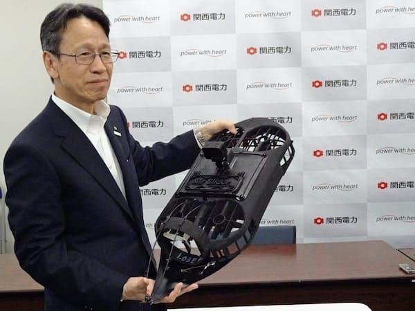 岩根茂樹社長が手に持つ水力鉄管の点検ドローンは「尻尾」の器具(写真下)が特徴(24日、大阪市)