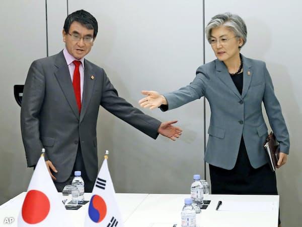 河野外相(左)は韓国側に早期の対応策提示を求めた(23日、パリ)=AP・共同