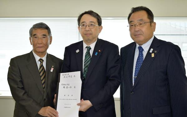 要望書を提出した佐藤昭会長(左)と橘慶一郎復興副大臣(中)(23日、仙台市)