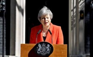 24日、首相官邸前で辞任を表明するメイ首相=ロイター