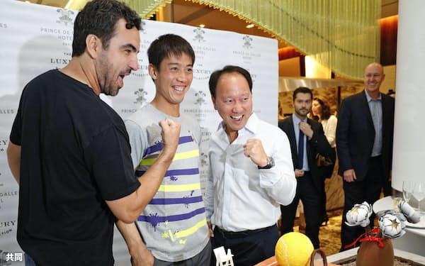 取材対応で写真に納まる錦織圭。右はマイケル・チャン・コーチ(24日、パリ)=共同