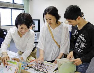 斎藤裕子さん(左)らが修復した思い出の品を受け取る小倉智美さん(中央)と息子の翔さん(25日午前、岡山市)=共同
