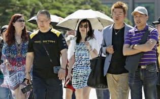 日傘を差して皇居付近を歩く女性ら(25日午前)=共同
