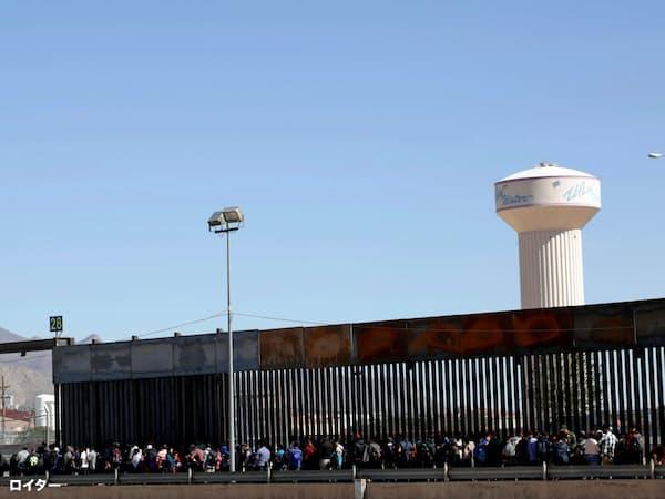 メキシコ国境で米国に不法入国した後、難民申請のために列をつくる人たち=ロイター