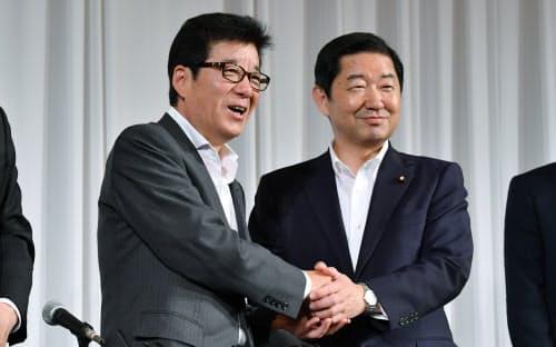 記者会見で握手する大阪維新の会の松井一郎代表(左)と公明党大阪府本部の佐藤茂樹代表(25日、大阪市北区)