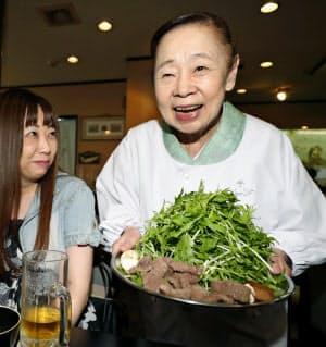 クジラ料理店「徳家」で料理を運ぶおかみの大西睦子さん(25日午後、大阪市)=共同