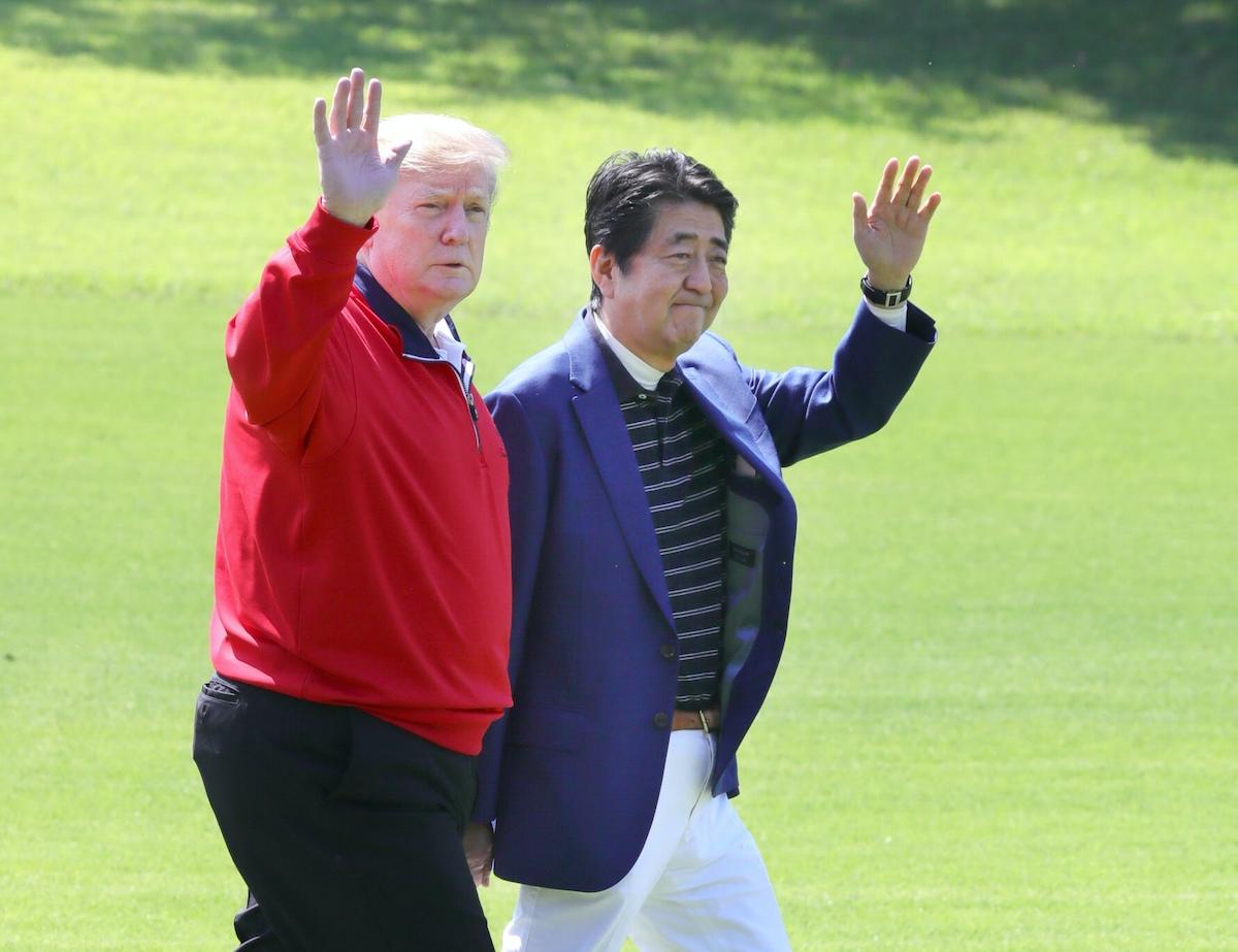 ゴルフ場で安倍首相の出迎えを受け、手を振るトランプ氏