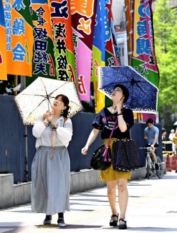 日傘を差して両国国技館前を歩く人たち(26日午前、東京・墨田)=共同