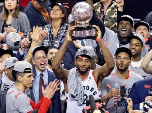 NBA決勝進出を決め、トロフィーを掲げて喜ぶラプターズのレナード=中央(25日、トロント)=カナディアンプレス提供・AP