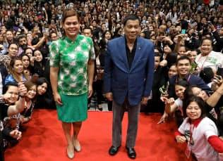 ドゥテルテ大統領(右)の香港訪問に同行し、現地に住むフィリピン人らに囲まれる長女のサラ・ダバオ市長(2018年4月)=フィリピン大統領府提供