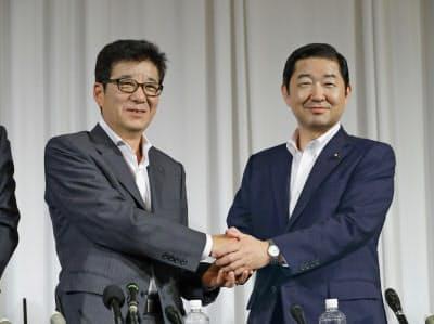 共同記者会見を終え、握手を交わす大阪維新の会代表の松井・大阪市長(左)と公明党大阪府本部代表の佐藤・衆院議員(25日、大阪市)=共同