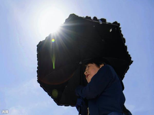 強い日差しの中、日傘を差してJR鳥栖駅前を歩く人(26日、佐賀県鳥栖市)=共同