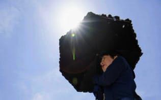 強い日差しの中、日傘を差してJR鳥栖駅前を歩く人たち=26日、佐賀県鳥栖市
