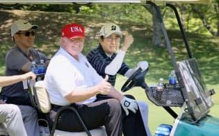 ゴルフカートで移動する安倍首相(右)とトランプ大統領(26日午前、千葉・茂原カントリー倶楽部)=内閣広報室提供・共同