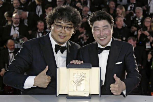 最高賞を受賞したポン・ジュノ監督(左)と「パラサイト」で父親役を演じたソン・ガンホ=ロイター