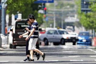 猛暑日となり、かげろうが立ち上る北海道帯広市の道路(26日)=共同