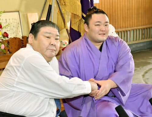 初優勝した大相撲夏場所の千秋楽から一夜明けた記者会見で、師匠の高砂親方(左)と握手する朝乃山(27日午前、東京都墨田区の高砂部屋)=共同