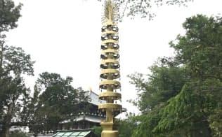 大阪万博「古河パビリオン」の七重塔先端の相輪。奥に見えるのが大仏殿(奈良市の東大寺)