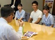 金足農業高校の生徒がローソンと共同開発したパンを試食する秋田県の佐竹敬久知事(左)(27日、秋田県庁)