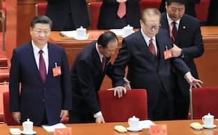 共産党大会に臨む習近平総書記(左)と体を支えられながら席に着く江沢民元国家主席(右から2人目)(2017年10月18日、北京の人民大会堂)=小高顕撮影