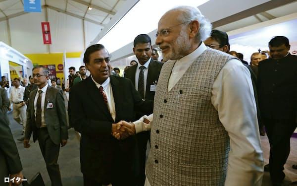 実業家のムケシュ・アンバニ氏と握手するモディ首相=右(16年2月)=ロイター