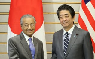 会談を前にマレーシアのマハティール首相(左)と握手する安倍首相(31日午前、首相官邸)