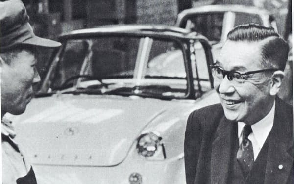 軽乗用車「R360クーペ」の組み立てラインで作業員と話す恒次(1960年)=「松田恒次追想録」から