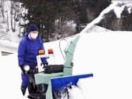 「歩行型ロータリ除雪機」を操作する男性(消費者安全調査委員会提供)=共同