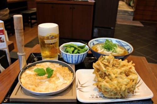 丸亀製麺の30分飲み放題では、1000円でうどんか親子とじのどちらかに加え、豊富な総菜から2品を選び、それらをつまみにビールなどを楽しめる