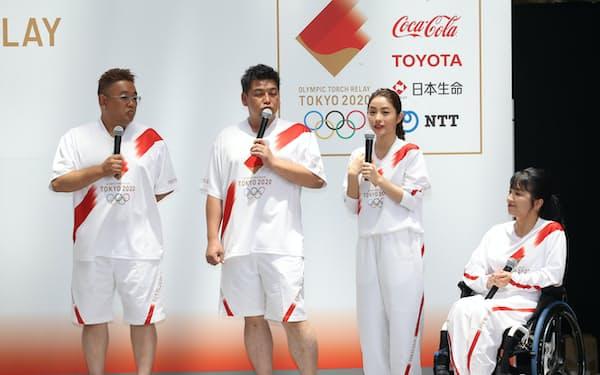 ユニホームを披露する東京2020聖火リレー公式アンバサダーの石原さとみさん(右から2人目)ら(1日午後、東京都港区)