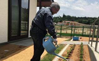 自宅の花壇に水やりをする新妻茂さん