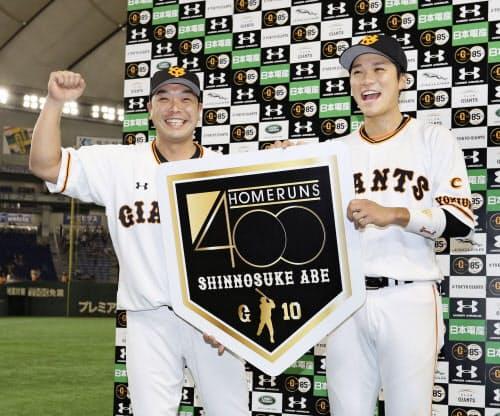 中日にサヨナラ勝ちし、お立ち台で通算400本塁打の記念ボードを手に笑顔を見せる巨人・阿部(左)と坂本勇(1日、東京ドーム)=共同