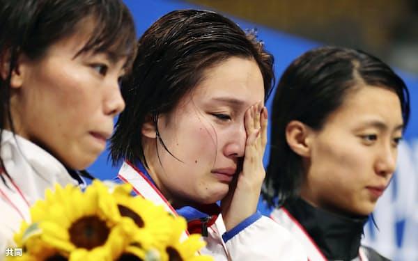 女子200メートル平泳ぎで優勝するも涙ぐむ渡部香生子(中央)。世界選手権の派遣標準記録を突破できなかった(2日、東京辰巳国際水泳場)=共同