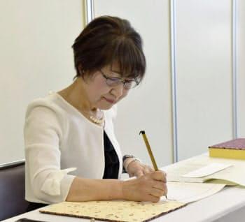 原爆死没者名簿に新たに死亡が確認された人の名前を書き加える森田さん(3日午前、長崎市役所)=共同